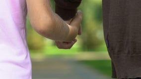 Viejo hombre que lleva a cabo las manos y que camina con su nieto el día de verano en parque almacen de video