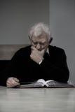 Viejo hombre que mira el álbum de foto Foto de archivo