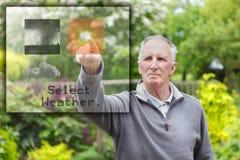 Viejo hombre que presiona la pantalla táctil Imagen de archivo libre de regalías