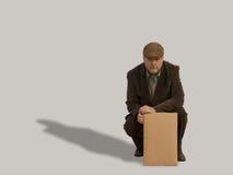 Viejo hombre que se agacha con la muestra en blanco Fotos de archivo libres de regalías