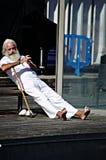 Viejo hombre que se relaja en el puerto de Barcelona Imagenes de archivo