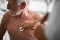 Viejo hombre que se sienta en cama de hospital durante el examen médico fotografía de archivo libre de regalías