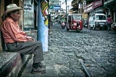 Viejo hombre que se sienta en una calle vieja del guijarro con el tráfico que conduce cerca Fotos de archivo libres de regalías