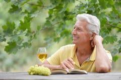 Viejo hombre que se sienta en una tabla Fotografía de archivo libre de regalías
