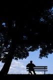 Viejo hombre que se sienta solamente en banco de parque debajo de árbol Imágenes de archivo libres de regalías