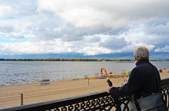 Viejo hombre que sostiene el paraguas del vintage que mira lejos Imagen de archivo libre de regalías