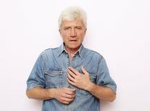 Viejo hombre que sostiene el pecho debido al infarto del coraz?n foto de archivo