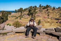 Viejo hombre que teje en los Andes peruanos en Puno Perú Fotografía de archivo