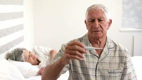 Viejo hombre que toma su temperatura almacen de metraje de vídeo