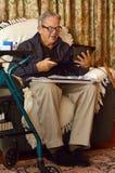 Viejo hombre que trabaja con el ordenador portátil en casa imagenes de archivo