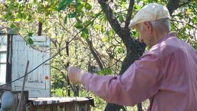 Viejo hombre que trabaja en su jard?n rural almacen de metraje de vídeo