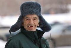 Viejo hombre ruso en sonrisas del sombrero del invierno imágenes de archivo libres de regalías