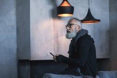 Viejo hombre sereno que mecanografía en móvil Foto de archivo libre de regalías