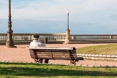 Viejo hombre solo que se sienta en el banco público, soledad de la orilla del agua Imagen de archivo