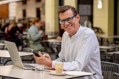 Viejo hombre sonriente que comprueba el teléfono elegante mientras que trabaja en el ordenador en cafetería del aire libre de la  foto de archivo