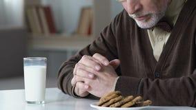 Viejo hombre triste que se sienta en la tabla que rechaza beber la leche, infeliz en clínica de reposo almacen de metraje de vídeo