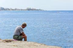 Viejo hombre triste que se sienta en las rocas por el mar España, Tenerife Fotografía de archivo libre de regalías