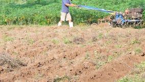 Viejo hombre usando un pequeño tractor para arar la granja para ajustar el suelo para que haya plantar almacen de video
