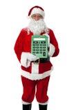 Viejo hombre vestido como Santa que muestra una calculadora imagen de archivo