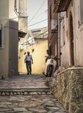 Viejo hombre y bici en callejón en pueblo viejo, griego Foto de archivo
