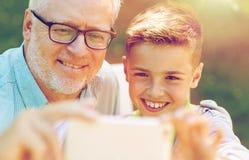 Viejo hombre y muchacho que toman el selfie por smartphone Fotos de archivo libres de regalías
