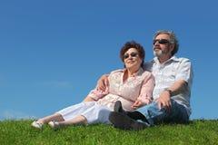 Viejo hombre y mujer en las gafas de sol que se sientan en césped Imágenes de archivo libres de regalías