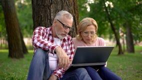 Viejo hombre y mujer que se sientan en hierba y el remolque de observación de la película de la novela de suspense en el ordenado imagen de archivo