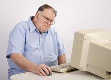 Viejo individuo en el ordenador que hace muecas Imágenes de archivo libres de regalías