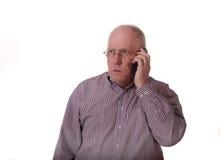 Viejo individuo en la camisa rayada que consigue malas noticias Foto de archivo libre de regalías