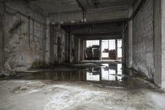 Viejo interior vacío del almacén Reflexiones en charco Imagen de archivo