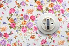 Viejo interruptor ligero en el papel pintado floral Foto de archivo