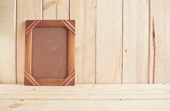 Viejo marco de la foto en la tabla de madera sobre el fondo de madera Fotografía de archivo libre de regalías