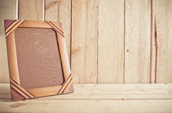 Viejo marco de la foto en la tabla de madera sobre el fondo de madera Imágenes de archivo libres de regalías