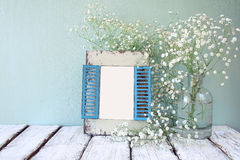 Viejo marco de madera al lado de las flores blancas en la tabla de madera la plantilla, alista para poner fotografía Fotos de archivo