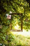 Viejo marco de oro, adornado con las flores, colgando en un fondo del verde de la rama Decoración floral para casarse la sesión f Fotografía de archivo