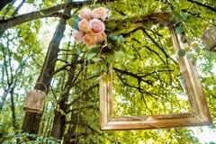 Viejo marco de oro, adornado con las flores, colgando en un fondo del verde de la rama Decoración floral para casarse la sesión f Foto de archivo libre de regalías