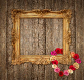 Viejo marco de oro con las rosas sobre fondo de madera Fotografía de archivo