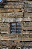 Viejo marco de ventana en una pared de madera del vintage en casa de la granja del aold Pared de madera vieja con el detalle de l Imágenes de archivo libres de regalías