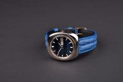 Viejo men& x27; reloj clásico de s con la correa azul en fondo negro Imágenes de archivo libres de regalías