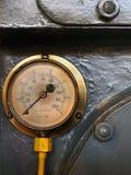 Viejo metro de cobre amarillo de la presión con una escala redonda con números en un dial envejecido en un fondo de acero gris fotografía de archivo