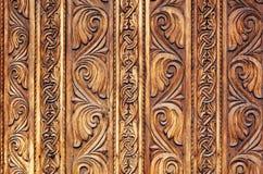 Viejo modelo de madera mano-tallado en una puerta del monasterio foto de archivo