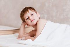 Viejo muchacho lindo Caucasoid de cinco años cubierto con la toalla de Terry blanca en dormitorio en el fondo blanco foto de archivo