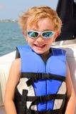 Viejo niño rubio 6yr con el chaleco salvavidas y los vidrios de sol imagen de archivo