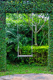 Viejo oscilación de madera del jardín del vintage que cuelga el fondo de la hierba verde Imagen de archivo