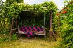 Viejo oscilación de madera en el jardín verde Fotos de archivo libres de regalías