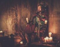Viejo rey medieval con el cubilete de vino en el trono en interior antiguo del castillo imagen de archivo