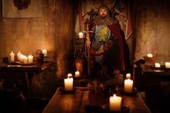 Viejo rey medieval en el trono en interior antiguo del castillo foto de archivo libre de regalías