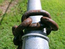 Viejo Rusty Chain Links en una cerca Pole del metal Imagen de archivo libre de regalías