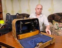 Viejo sastre Man Closing un caso con la máquina de coser Imagenes de archivo