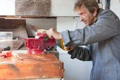 Viejo sawing mayor del hombre en vertiente del taller Fotos de archivo libres de regalías